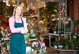 A smiling woman standing in front of a floral shop with arms crossed